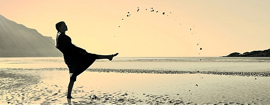 Frau kickt Sand am Strand